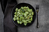 Spinach and basil gnocchi with sage in a black bowl on a grey surface