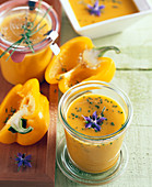 Yellow pepper soup with borage flowers in jars