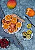 Fresh fruits: blood oranges, mango, persimmons, kiwis and iced berries