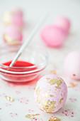 Rosafarbene Eier mit Blattgold und Schälchen mit Farbe