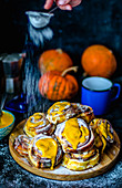 Cinnabons with pumpkin and pumpkin puree sauce with cream and powdered sugar