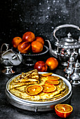 Custard pancakes on kefir with slices of red orange and fresh red oranges