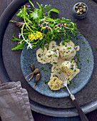 Vegetarian grain dumplings with caper sauce and garden salad