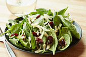 A spinach salad with goat's cheese cheddar and dried cranberries