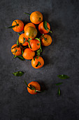 Mandarins with leaves on a grey surface