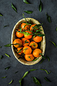 Mandarins with leaves in an oval basket on a grey surface