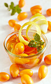 Homemade kumquat vinegar with lemon peel and mint