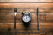 Fork and knife lying on wooden tabletop near mechanical alarm clock