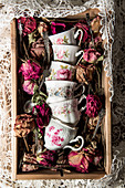 Vintage cups with floral motifs and dried flowers