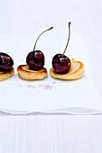 Mini potato blinis with glazed cherries