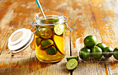 Homemade limequat vinegar with fresh limes in a glass