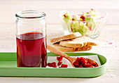 Homemade sour cherry vinegar in a glass, with salad and white bread