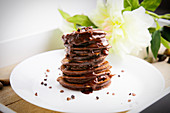 A stack of chocolate pancakes with chocolate sauce