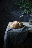 A loaf of olive bread on a linen cloth