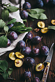 Damsons on a dark wooden surface with a linen cloth and a knife