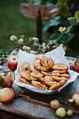 Baked apple rings on a wooden table in a garden
