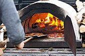 Sliding pizzas into a small portable wood-fired pizza oven with live flame and coals
