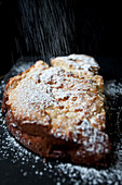An apple cake on a black board, being dusted with powdered sugar