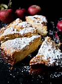 Apple cake slices, dusted with powdered sugar, on a black surface, with red apples