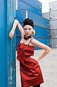Junges blondes Model im roten Abendkleid und mit schwarzem Kopftuch