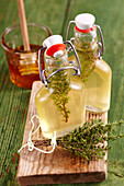 Homemade thyme vinegar with honey in small glasses on a wooden board