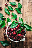 Flat lay of ceramic bowl filled with wet shiny cherry and composed with green leaves on rustic table