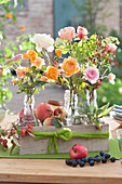Herbstliche Sträuße mit Rosen, Hagebutten, Fetthenne und Salbei in Flaschen