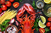 Steamed red lobster with spaghetti, red ripe cherry tomatoes, lemon wedges and parsley