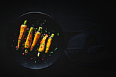 Healthy roasted carrots on dark background
