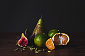 Tasty fresh peeled tangerines, fig, pear and nutmegs on board on black background