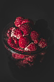 Yummy ripe raspberries lying in glass jar in dark room
