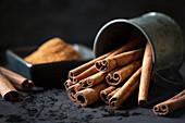 Bunch of aromatic cinnamon sticks lying in metal cup on dark tabletop