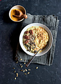 Delicious oatmeal porridge with turmeric and grain standing on napkin on dark tabletop