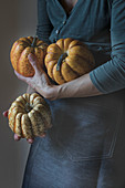 Woman holding three tiny pumpkins while standing on gray background