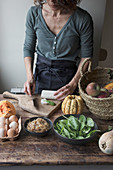 Woman cutting ingredients for tasty pumpkin and spinach frittata while standing near wooden table