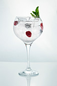 Crystal wineglass filled with ice and drink with ripe raspberry garnished with mint on white background