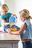 Kinder machen gemeinsam Puffreis-Gebäckschnitten