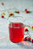Rosehip tea in a glass cup with fresh rosehips