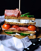 A sandwich with cheese, sausage and vegetables