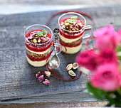 Vegan layered dessert in jars with granola, vanilla yoghurt cream and raspberries