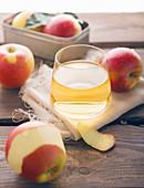Ein Glas Apfelsaft, drumherum frische Äpfel