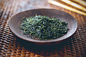 Green tea: tea leaves in a wooden bowl