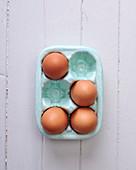 Vier Eier in Porzellan-Eierbehälter