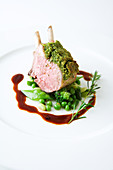 Lamb chop with a bean crust on green vegetables