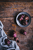 Small violet artichokes on a cloth and a wooden surface