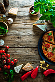 Italian pizza ingredients with cheese, tomatoes and basil