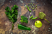 Mix of fruits and vegetables in green color on rusty background
