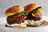 Burgers with grilled beef patties, cream cheese and spinach on classical bun