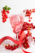 Homemade redcurrant liqueur with a ribbon and fresh berries