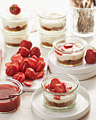 Mini strawberry cheesecakes in glasses with an amarettini base